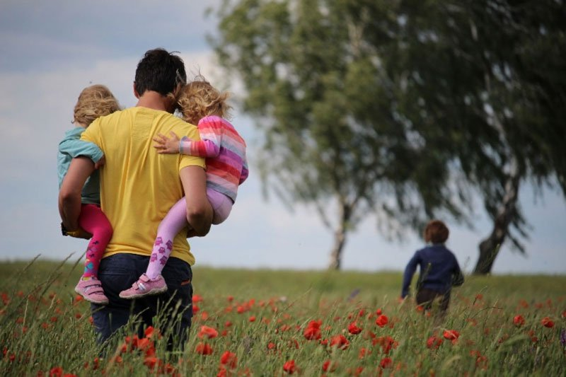 Man with children in field of flowers